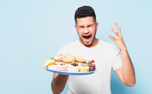 Jonge spaanse man boze uitdrukking met cupcakes