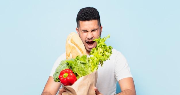 Jonge spaanse man boze uitdrukking. winkelen groenten concept