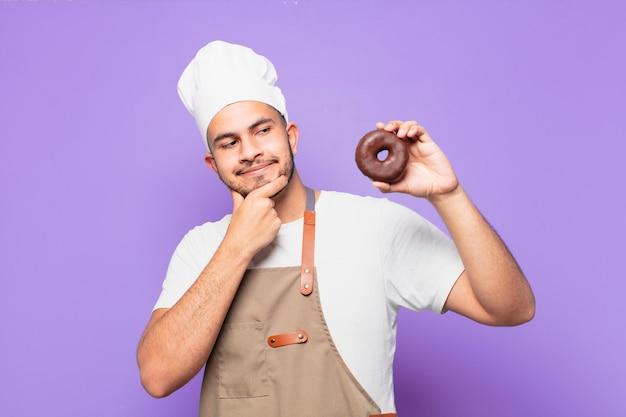 Jonge spaanse man denken expressie. chef of bakker concept