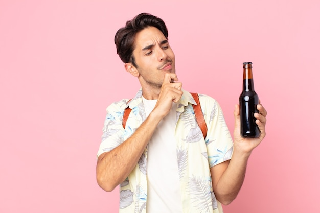 Jonge spaanse man denkt, voelt zich twijfelachtig en verward en houdt een flesje bier vast