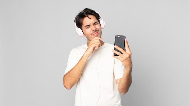 Jonge spaanse man denkt, voelt zich twijfelachtig en verward met koptelefoon en smartphone