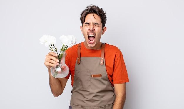 Jonge spaanse man die agressief schreeuwt en er erg boos uitziet. bloemist concept