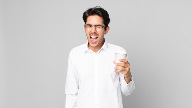 Jonge spaanse man die agressief schreeuwt, erg boos kijkt en een afhaalkoffie vasthoudt
