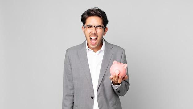 Jonge spaanse man die agressief schreeuwt, erg boos kijkt en een spaarvarken vasthoudt