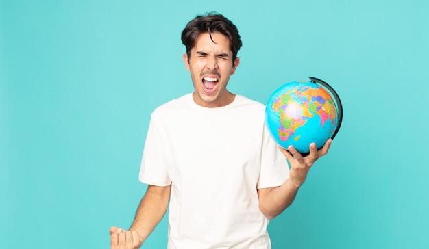Jonge spaanse man die agressief schreeuwt, erg boos kijkt en een wereldbolkaart vasthoudt