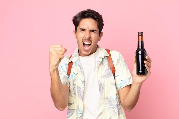 Jonge spaanse man die agressief schreeuwt met een boze uitdrukking en een flesje bier vasthoudt