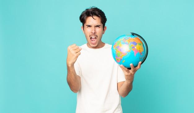 Jonge spaanse man die agressief schreeuwt met een boze uitdrukking en een wereldbolkaart vasthoudt