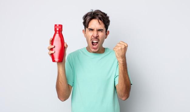 Jonge spaanse man die agressief schreeuwt met een boze uitdrukking. ketchup-concept
