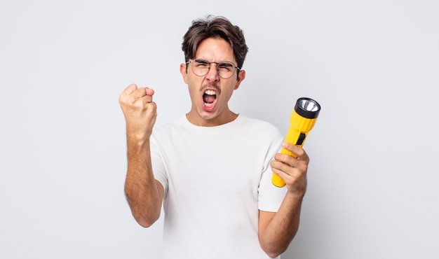 Jonge spaanse man die agressief schreeuwt met een boze uitdrukking. lantaarn concept