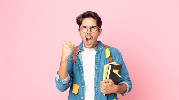 Jonge spaanse man die agressief schreeuwt met een boze uitdrukking. studentenconcept