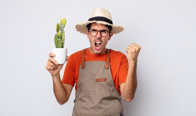 Jonge spaanse man die agressief schreeuwt met een boze uitdrukking. tuinman met cactusconcept