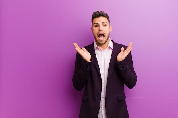Jonge spaanse man die blij en opgewonden kijkt, geschokt met een onverwachte verrassing met beide handen open naast het gezicht