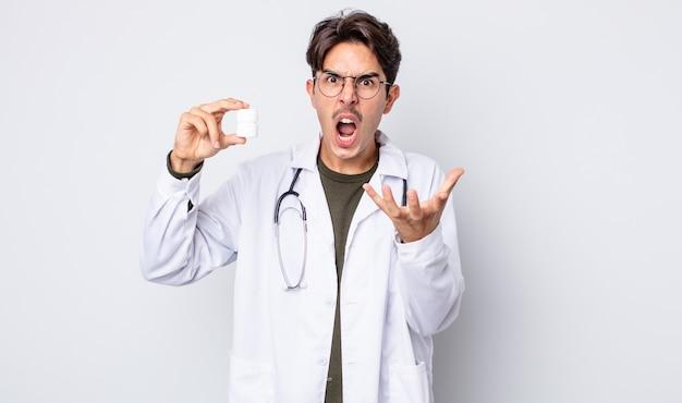 Jonge spaanse man die boos, geïrriteerd en gefrustreerd kijkt. arts met pillen fles concept
