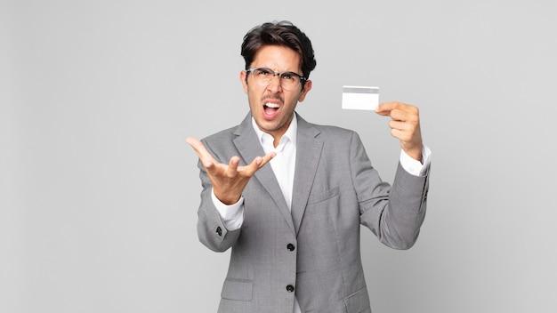 Jonge spaanse man die boos, geïrriteerd en gefrustreerd kijkt en een creditcard vasthoudt