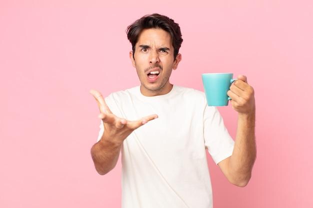 Jonge spaanse man die boos, geïrriteerd en gefrustreerd kijkt en een koffiemok vasthoudt