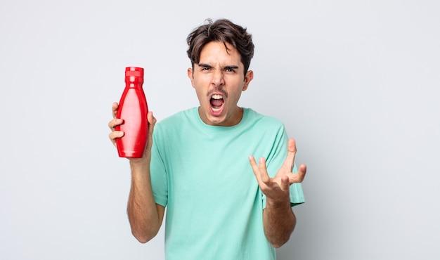 Jonge spaanse man die boos, geïrriteerd en gefrustreerd kijkt. ketchup-concept