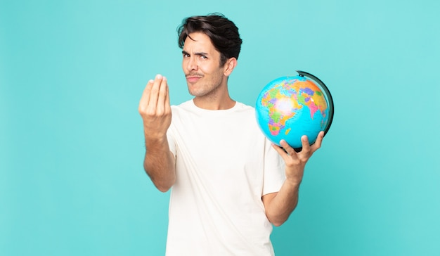 Jonge spaanse man die capice of geldgebaar maakt, zegt dat je moet betalen en een wereldbolkaart vasthoudt