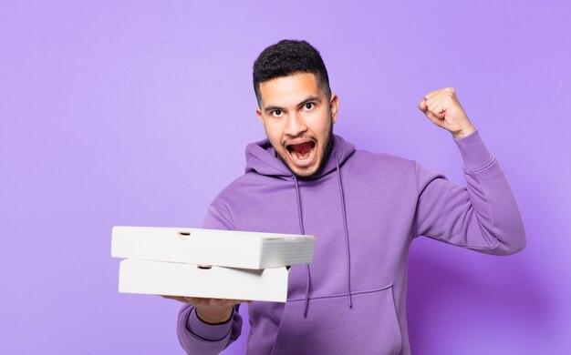 Jonge spaanse man die een succesvolle overwinning viert en afhaalpizza's vasthoudt