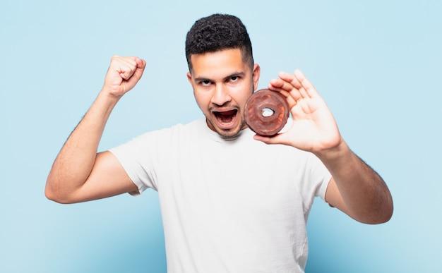Jonge spaanse man die een succesvolle overwinning viert en een donut vasthoudt