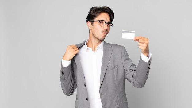 Jonge spaanse man die er arrogant, succesvol, positief en trots uitziet en een creditcard vasthoudt