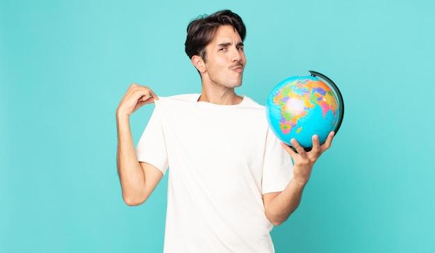 Jonge spaanse man die er arrogant, succesvol, positief en trots uitziet en een wereldbolkaart vasthoudt
