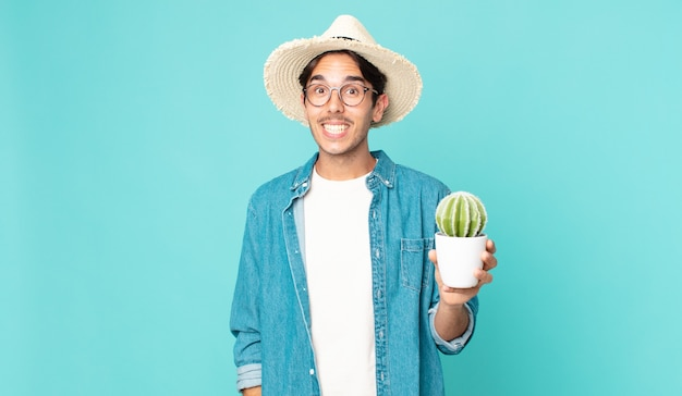 Jonge spaanse man die er blij en aangenaam verrast uitziet en een cactus vasthoudt