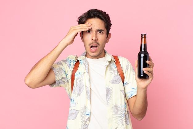 Jonge spaanse man die er blij, verbaasd en verrast uitziet en een flesje bier vasthoudt