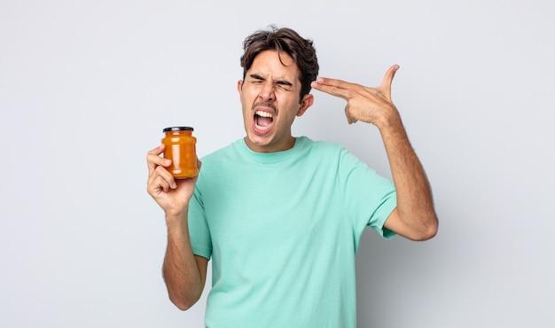 Jonge spaanse man die er ongelukkig en gestrest uitziet, zelfmoordgebaar dat een pistoolteken maakt. perzik gelei concept
