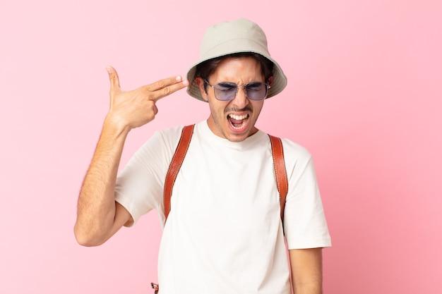 Jonge spaanse man die er ongelukkig en gestrest uitziet, zelfmoordgebaar dat een pistoolteken maakt. zomer concept