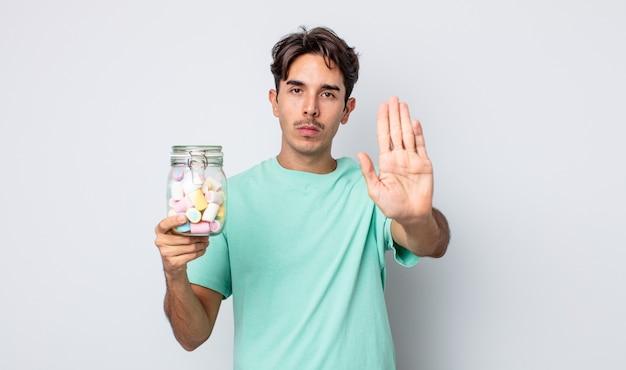 Jonge spaanse man die er serieus uitziet en een open palm toont die een stopgebaar maakt. gelei snoepjes concept