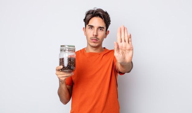 Jonge spaanse man die er serieus uitziet en een open palm toont die een stopgebaar maakt. koffiebonen concept
