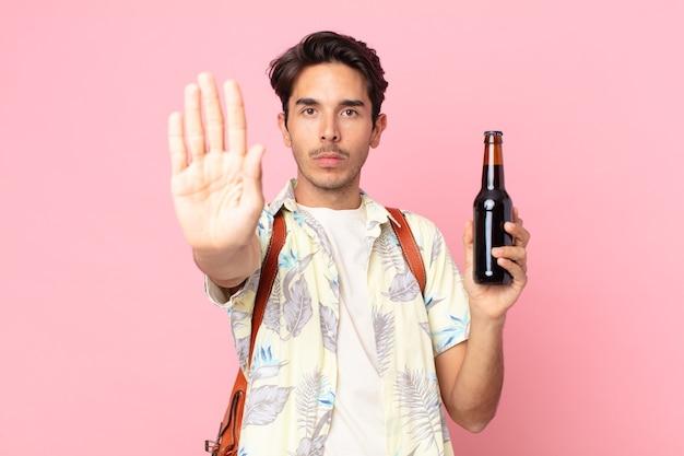 Jonge spaanse man die er serieus uitziet met een open palm die een stopgebaar maakt en een flesje bier vasthoudt