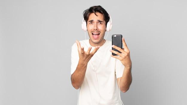 Jonge spaanse man die er wanhopig, gefrustreerd en gestrest uitziet met koptelefoon en smartphone
