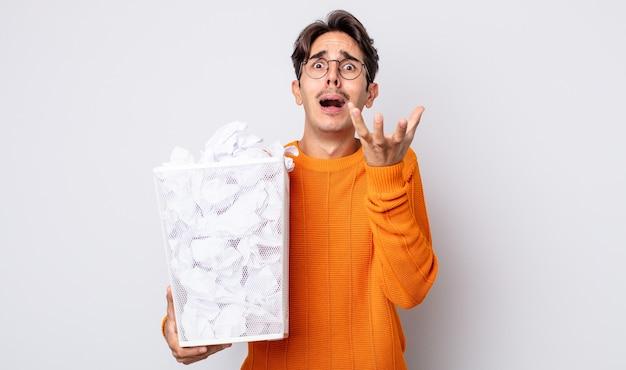 Jonge spaanse man die er wanhopig, gefrustreerd en gestrest uitziet. papier ballen prullenbak concept