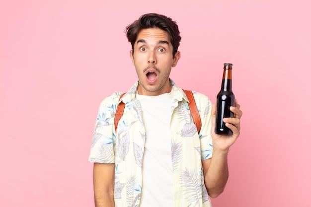 Jonge spaanse man die erg geschokt of verrast kijkt en een flesje bier vasthoudt