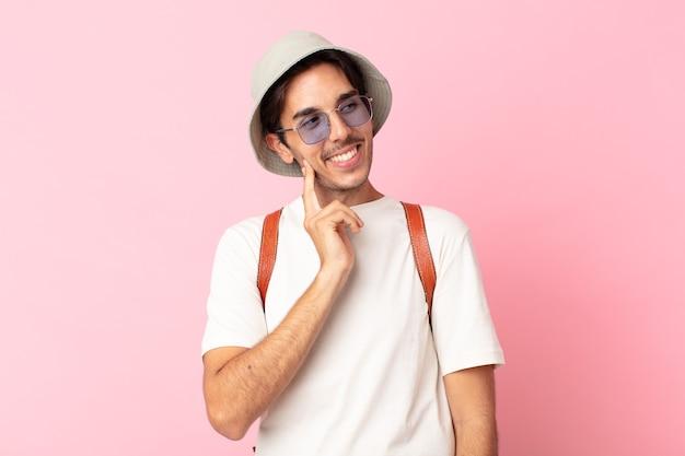 Jonge spaanse man die gelukkig lacht en dagdroomt of twijfelt. zomer concept