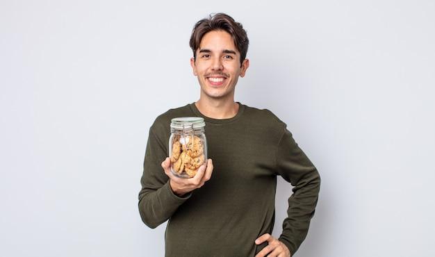 Jonge spaanse man die gelukkig lacht met een hand op de heup en zelfverzekerd. koekjes concept