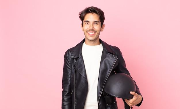Jonge spaanse man die gelukkig lacht met een hand op de heup en zelfverzekerd. motorrijder concept