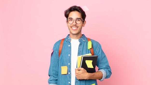 Jonge spaanse man die gelukkig lacht met een hand op de heup en zelfverzekerd. studentenconcept