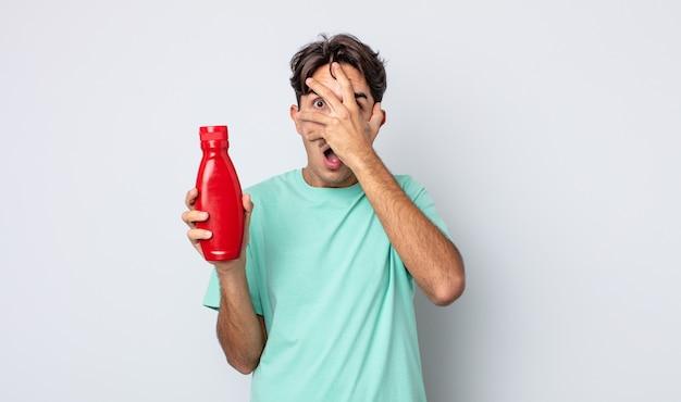 Jonge spaanse man die geschokt, bang of doodsbang kijkt en zijn gezicht bedekt met de hand. ketchup-concept
