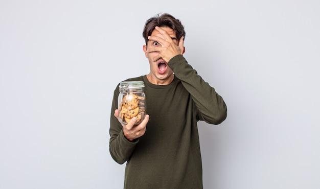 Jonge spaanse man die geschokt, bang of doodsbang kijkt en zijn gezicht bedekt met de hand. koekjes concept
