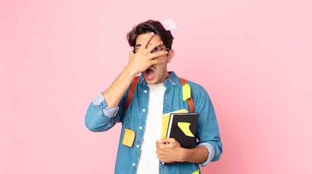 Jonge spaanse man die geschokt, bang of doodsbang kijkt en zijn gezicht bedekt met de hand. studentenconcept