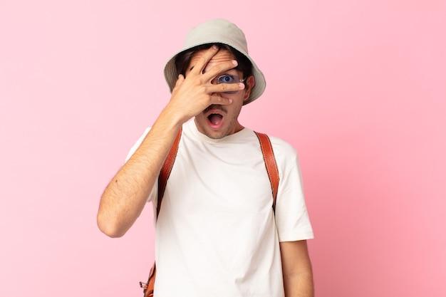 Jonge spaanse man die geschokt, bang of doodsbang kijkt en zijn gezicht bedekt met de hand. zomer concept