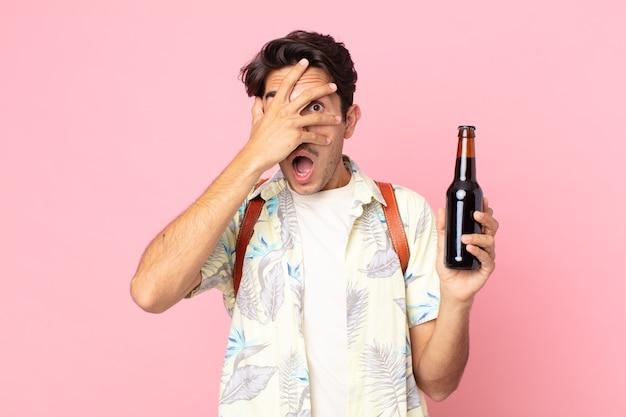 Jonge spaanse man die geschokt, bang of doodsbang kijkt, zijn gezicht bedekt met de hand en een flesje bier vasthoudt