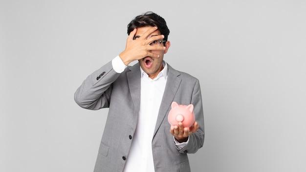 Jonge spaanse man die geschokt, bang of doodsbang kijkt, zijn gezicht bedekt met de hand en een spaarvarken vasthoudt
