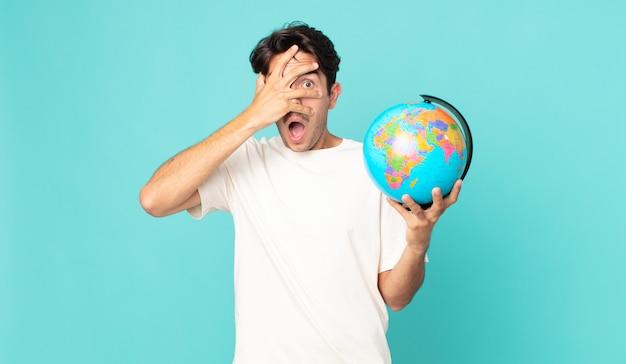 Jonge spaanse man die geschokt, bang of doodsbang kijkt, zijn gezicht bedekt met de hand en een wereldbolkaart vasthoudt