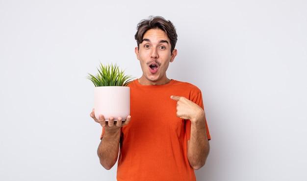 Jonge spaanse man die geschokt en verrast kijkt met wijd open mond, wijzend naar zichzelf. decoratief plantenconcept