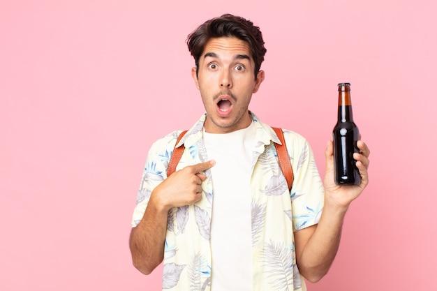 Jonge spaanse man die geschokt en verrast kijkt met wijd open mond, wijzend naar zichzelf en een flesje bier vasthoudend