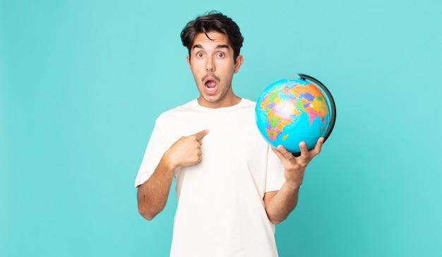 Jonge spaanse man die geschokt en verrast kijkt met wijd open mond, wijzend naar zichzelf en een wereldbolkaart vasthoudend
