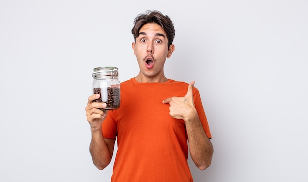Jonge spaanse man die geschokt en verrast kijkt met wijd open mond, wijzend naar zichzelf. koffiebonen concept